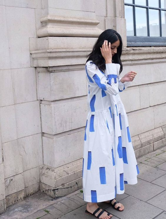 a minimalist midi dress in blue and white, with an abstract print, black slippers for a summer look