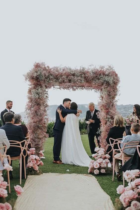 a pink baby's breath wedding arch and pink floral arrangements create a very romantic and beautiful wedding ceremony space