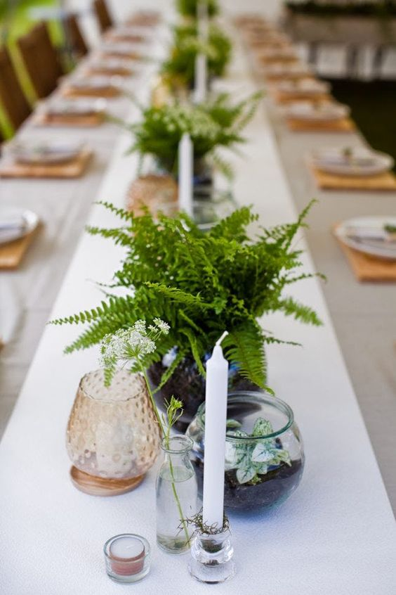 a pretty and easy wedding centerpiece of fern leaves, some potted greenery and a candle in a candlholder for a modern woodland wedding
