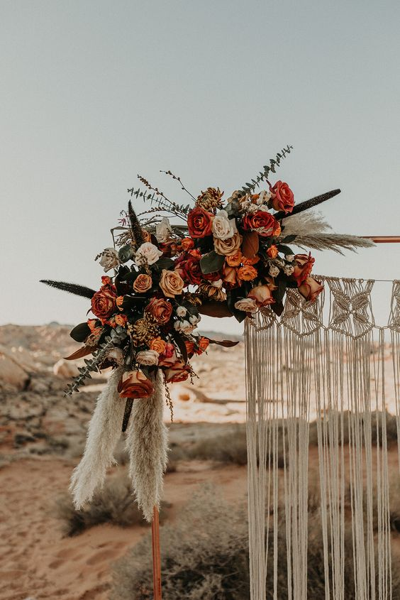 a pretty wedding arch with macrame and fringe, rust and burgundy blooms, greenery and pampas grass