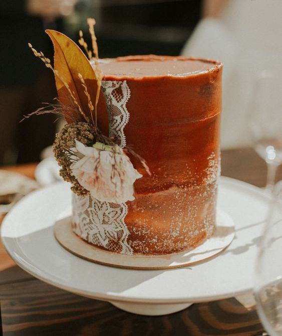 a rust textural wedding cake with sugar powder, lace, fresh and dried bloomsand grass for a fall boho wedding