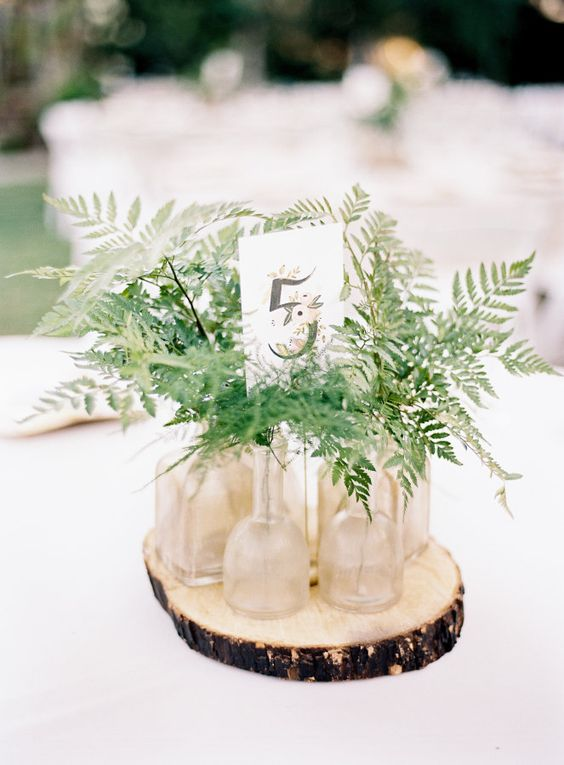 a very simple cluster wedding centerpiece of a wood slice, bottles and vases with fern leaves and a table number is all cool