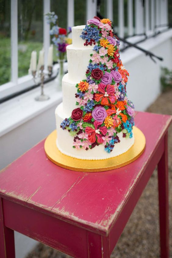 a white wedding cake with colorful sugar blooms and leaves is a bold and cool idea for a summer wedding in bold shades