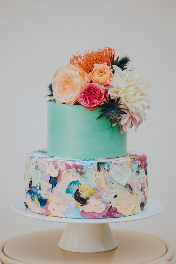 a beautiful colorful wedding cake with a mint green and bold textural brushstroke tier, bold blooms and thistles on top