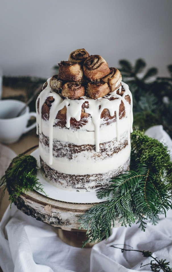 a delicious cinnamon roll wedding cake styled as a usual naked one, with white frosting and some cinnamon buns on top