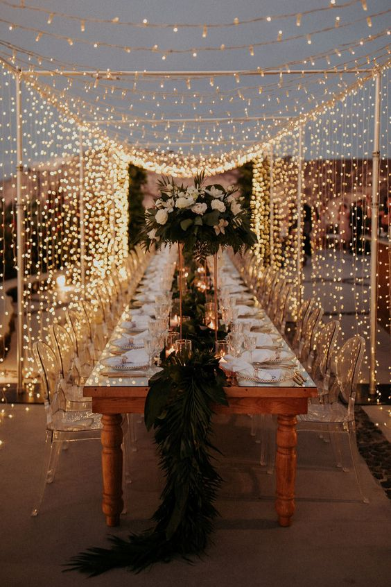 a fantastic outdoor wedding reception with a vintage table, clear acrylic chairs and a light canopy over the table