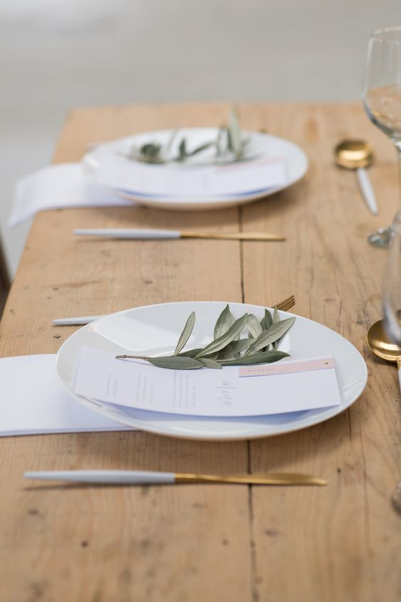 a minimalist Scandinavian wedding tablescape with white plates, gold cutlery, greenery, white linens and an uncovered table