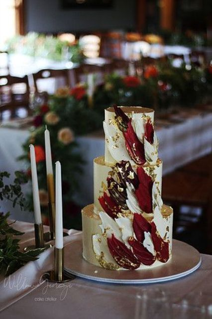a neutral wedding cake with white and burgundy gilded brushstrokes for a refined and bold wedding, a fall or winter one