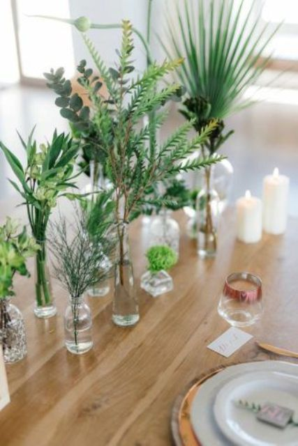12 a pretty and fresh cluster wedding centerpiece with bottles and vases and various types of greenery plus candles is very cool