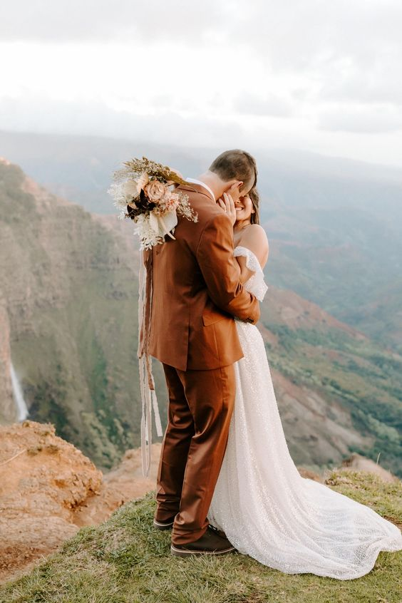 a rust-colored suit, a white shirt, black shoes for a simple, stylish and bold look at a boho wedding