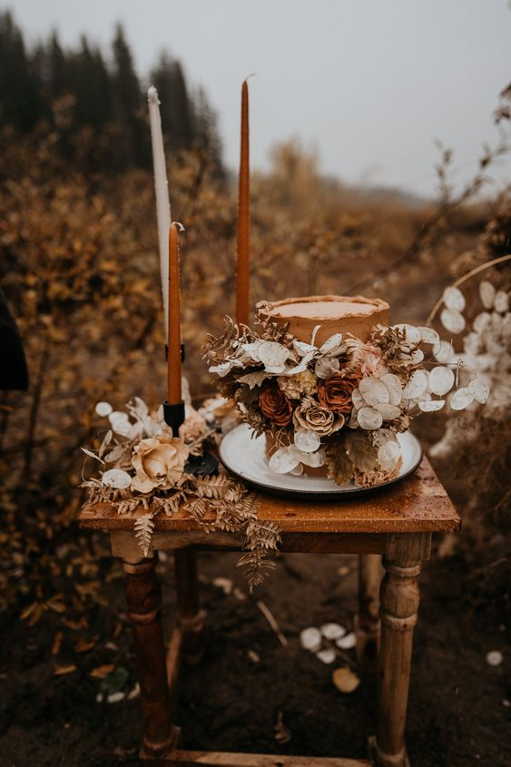 a rust wedding cake lushly decorated with white, yellow and rust blooms, dried grasses and foliage for a fall boho wedding