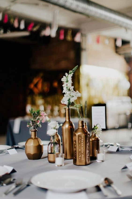 an elegant cluster wedding centerpiece of gold vases and bottles, neutral and pastel blooms is a chic and modern idea