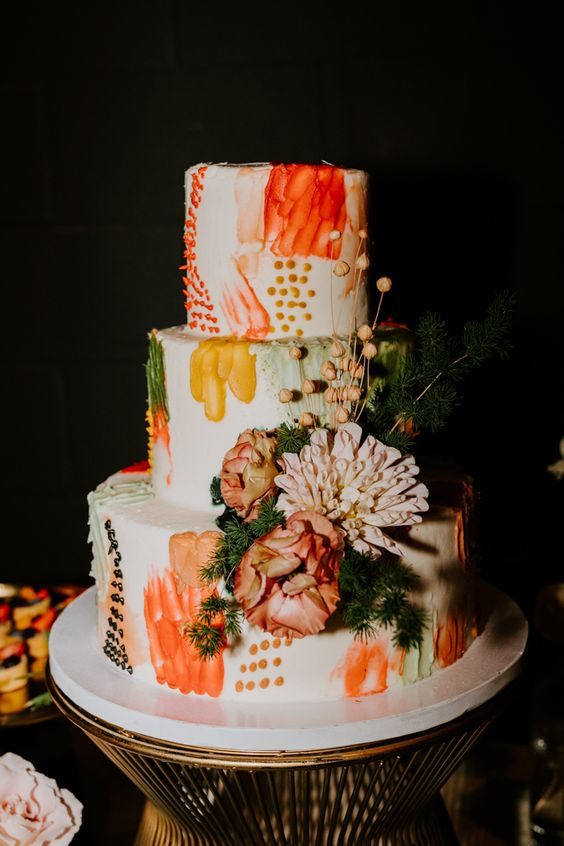 a bold color block wedding cake with orange, mustard, rust and green detailing, fresh blooms and berries and greenery