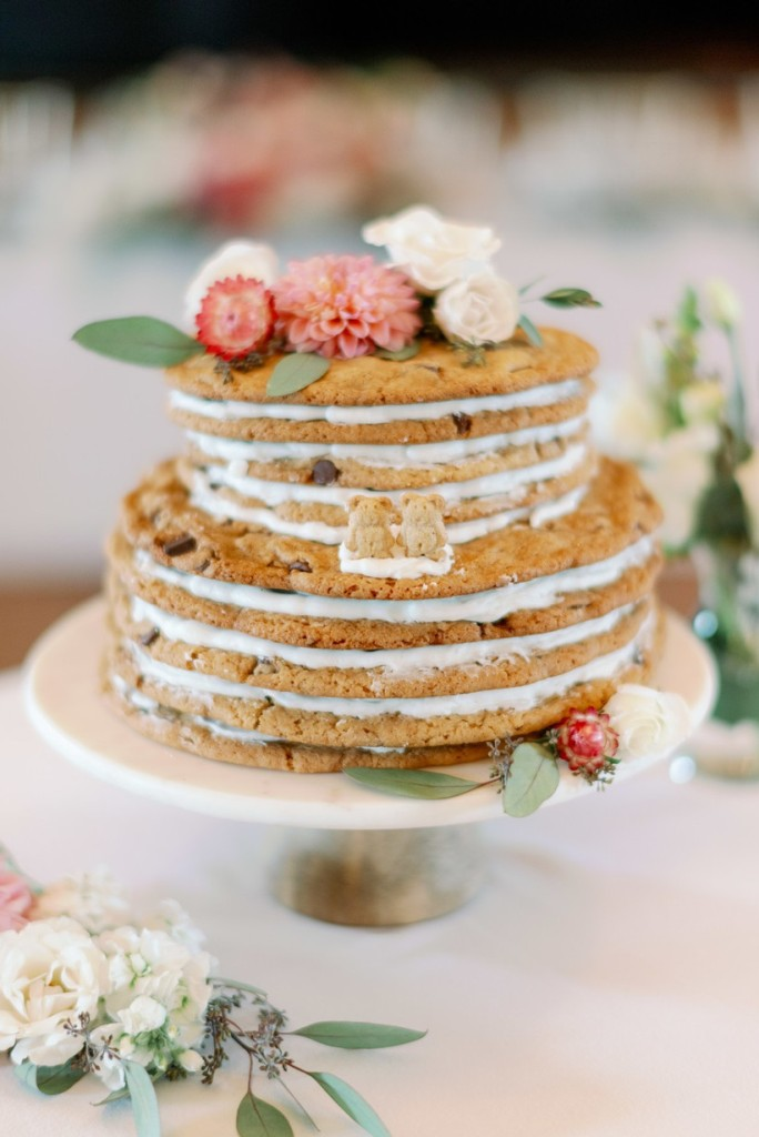 a cookie wedding cake with white filling, fresh blooms and foliage on top and little bear cookies as toppers is all cute