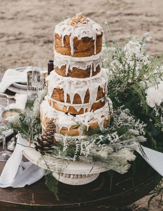 a fantastic cinnamon roll wedding cake with several tiers, white icing, some greenery and pinecones is a lovely idea