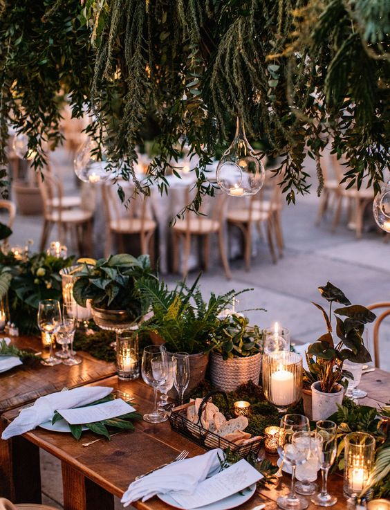 a lush cluster wedding centerpiece of potted greenery and candles plus an overhead greenery installation with candles is chic