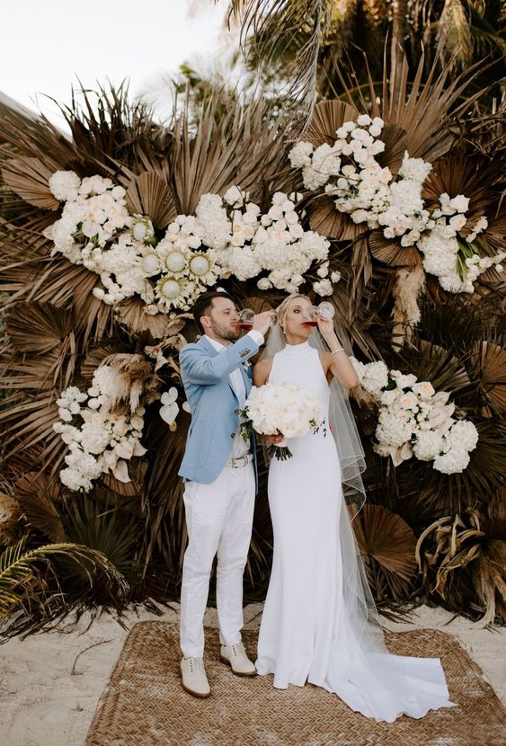 a luxurious boho wedding backdrop of dried fronds, white blooms and some grasses for a tropical boho wedding