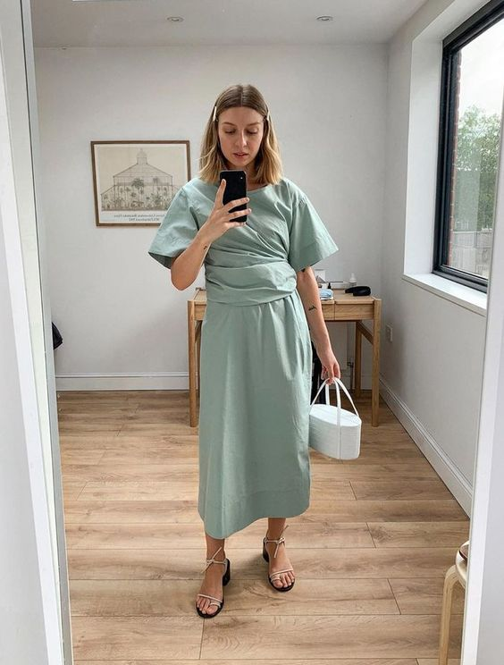 a mint midi draped dress with a high neckline and short sleeves, white heels, a bucket bag and hair accessories
