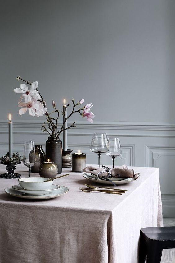 a moody Scandinavian spring tablescape with pink linens, dark vases and candleholders, pink cherry blossom and refined candleholders