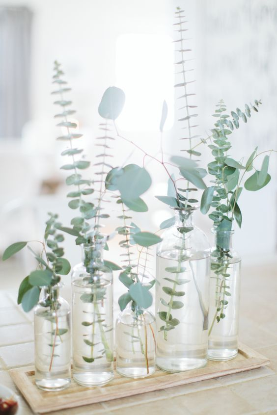 a pretty and simple cluster wedding centerpiece of bottles and with fresh eucalyptus is a great solution for a modern wedding