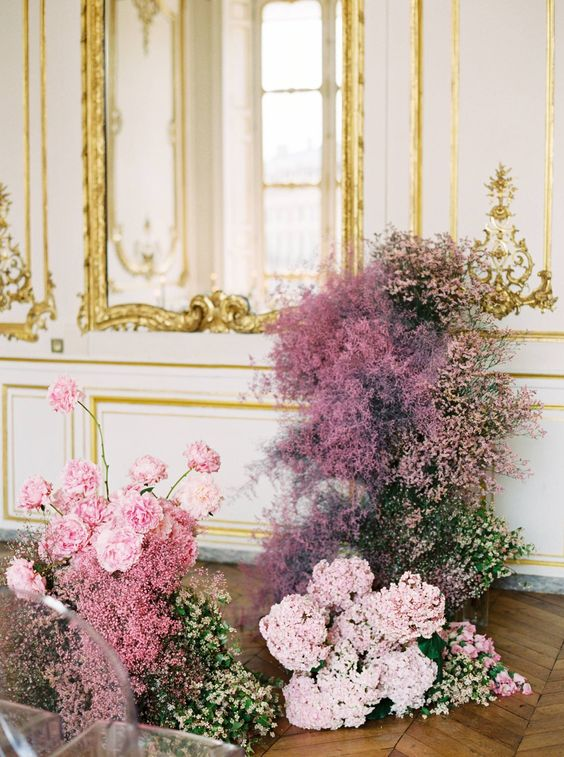 a refined wedding altar with blush and pink baby's breath and other blooms looks very cohesive with the space around it
