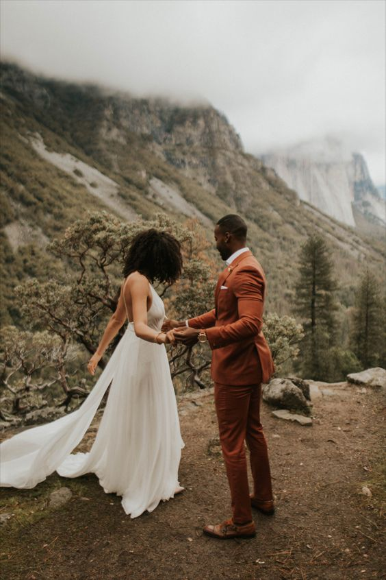 a rust-colored suit, a white shirt, brown shoes and a floral boutonniere for a boho groom's look