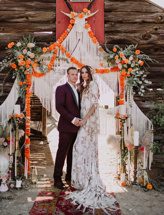 an incredible boho wedding arch with fringe, bold blooms, greenery, a faux skull and candles around for a flower child wedding