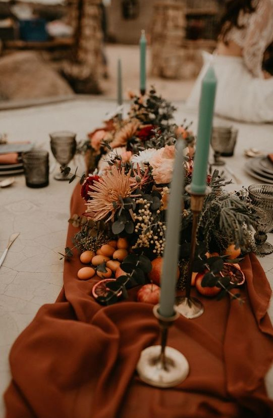 a beautiful wedding table runner with rust fabric, blush and white blooms, fruits, mint candles
