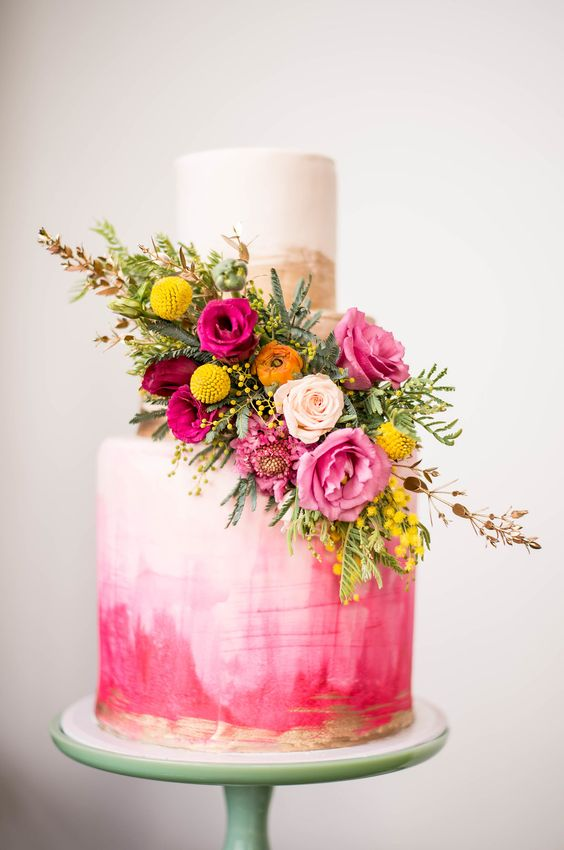 a bold pink watercolor wedding cake with brushstrokes, gold brushstrokes, bold pink, yellow and orange blooms and greenery