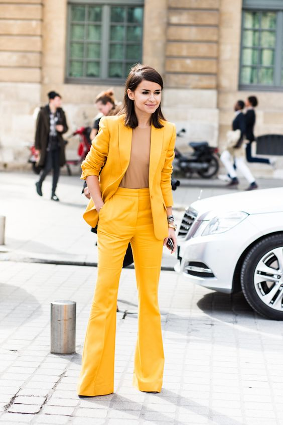 a bright yellow suit with flare pants, a camel top that matches the skin and a small clutch