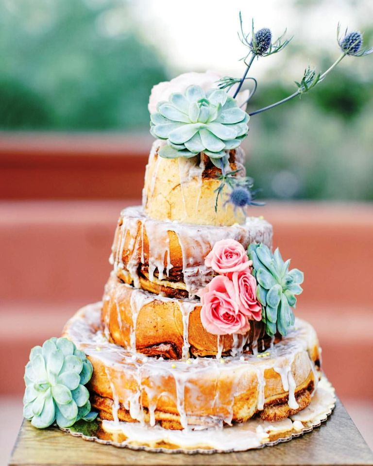 a fantastic cinnemon roll wedding cake with white icing, pink blooms, succulents and thistles for a summer wedding