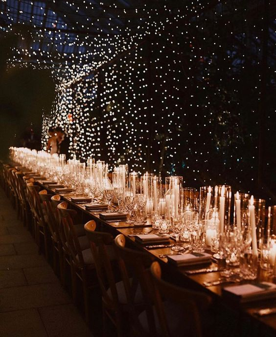 a gorgeous lit up wedding reception with a light canopy and lots of candles along the tables is wow