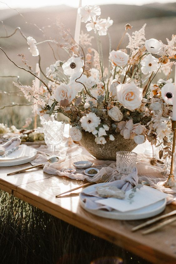 a neutral Scandi summer tablescape with pastel linens, neutral porcelain, a lush floral centerpiece, candles and copper cutlery
