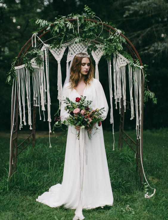 a pretty boho wedding arch with a curved top, macrame, greenery and fringe is a lovely idea for a boho 70s wedding