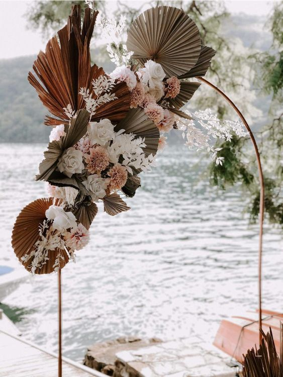 a refined wedding arch done with fresh and dried palm leaves, white and pink blooms and dried foliage is a very cool idea