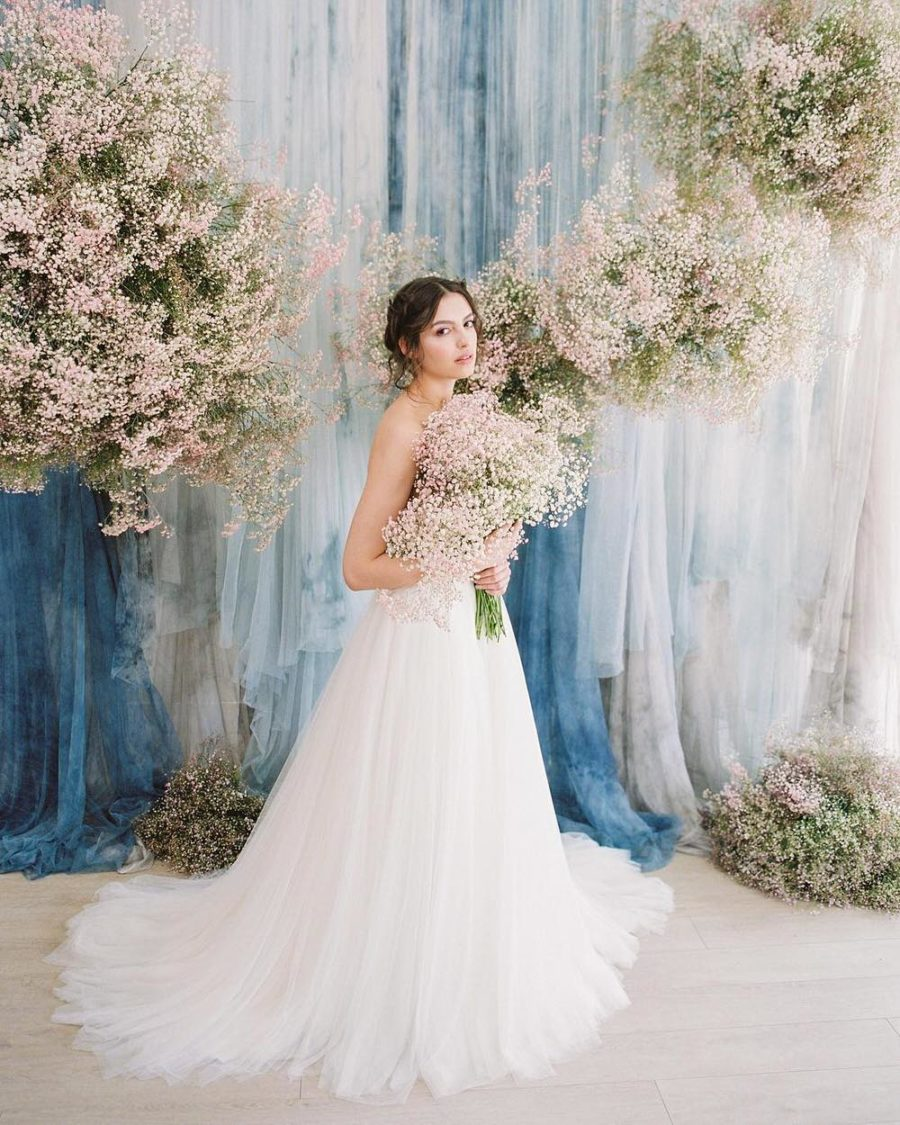 a romantic wedding backdrop with blue and white tie-dye fabric and blush baby's breath around is a very beautiful idea