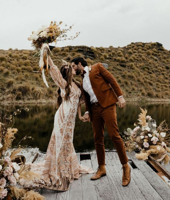 a rust-colored suit, a white shirt, tan shoes and a bow tie plus a floral boutonniere for a fall boho wedding