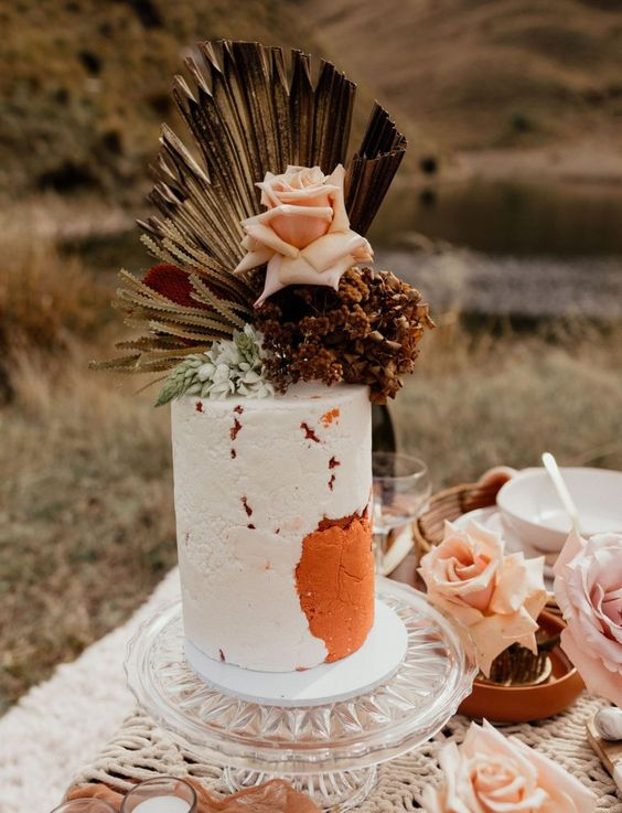 a statement wedding cake in white and rust, with a texture, fresh and dried blooms and fronds on top for a gorgeous boho wedding