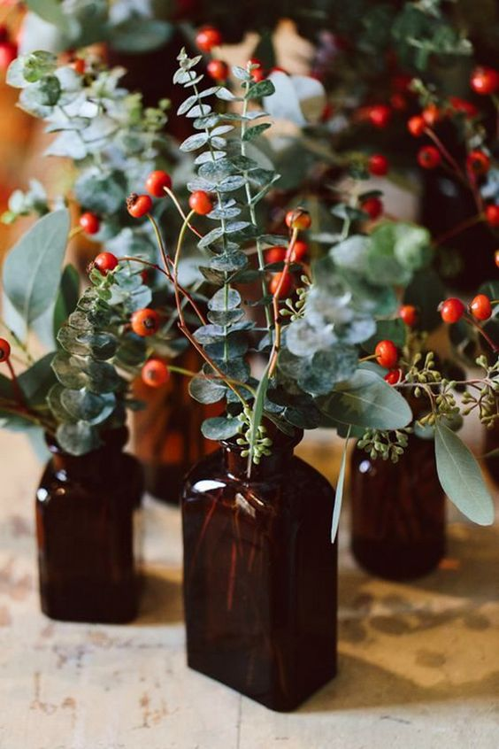14 apothecary bottles and eucalyptus and berries make up a cool and bold wedding centerpiece with a rustic feel