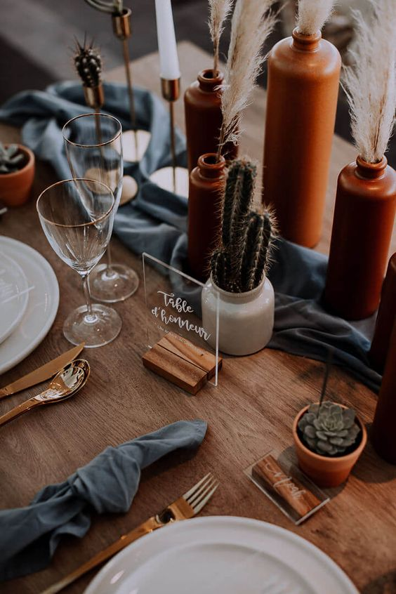 a boho desert wedding tablescape with terracotta vases, pampas grass, cacti and succulents, wooden stands and touches of slate grey