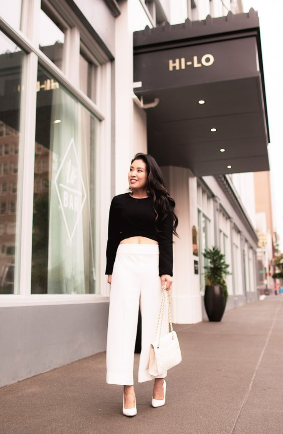 a bold and chic minimalist outfit with a black crop top, white wideleg pants, white shoes and a white bag