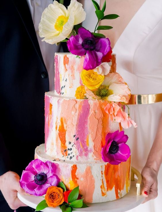 a bold wedding cake with colorful dimensional brushstrokes plus bold flowers and greenery is a vivacious idea to rock