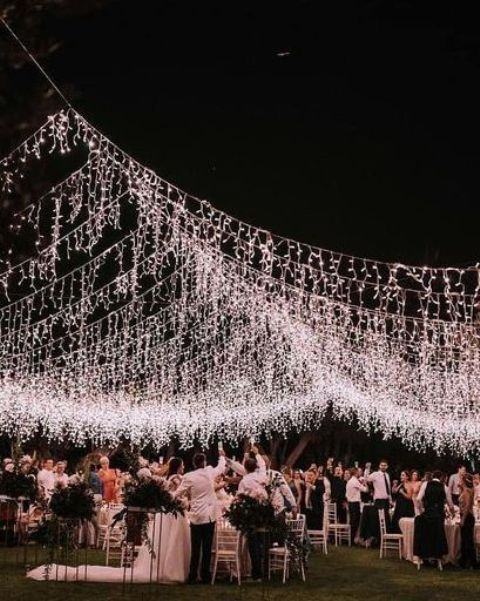 a gorgeous warm white wedding light canopy over the reception with some lights hanging down to bring even more light