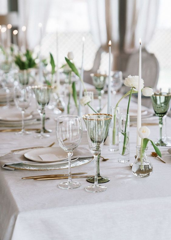 a refined and minimal Scandinavian tablescape with white candles, cluster centerpieces with white blooms, neutral porcelain
