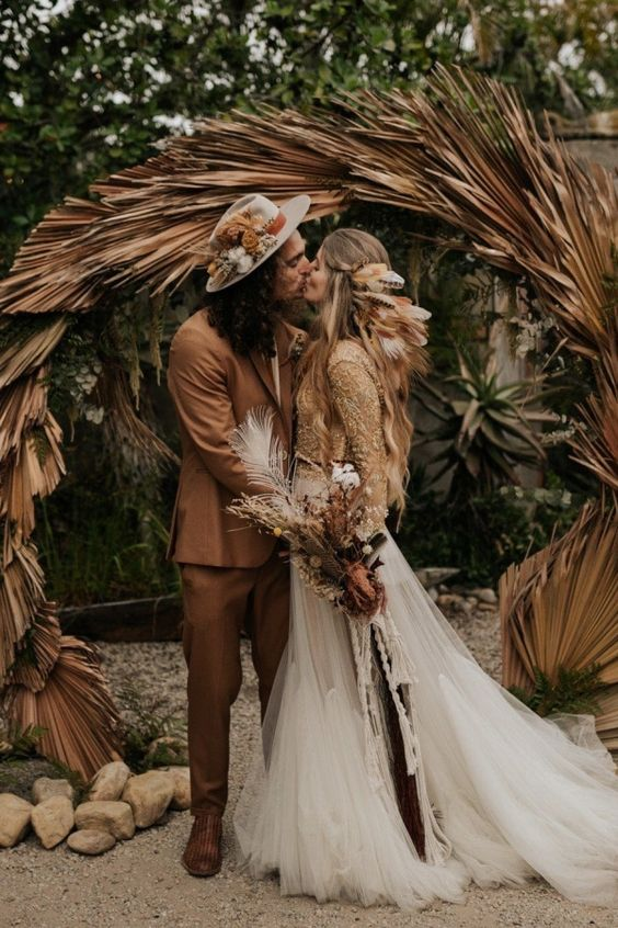 a round boho wedding arch fully covered with dried fronds is a lovely idea for a boho tropical wedding to rock