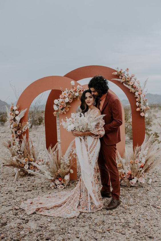 a rust-colored suit, an orange turtleneck, brown shoes for a bold boho desert wedding with a relaxed feel