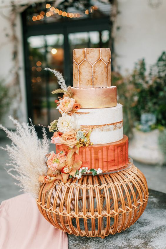 a statement wedding cake with an orange, white naked, rust patterned tiers, bright orange blooms and greenery