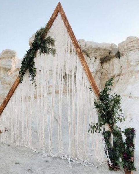 a triangle wedding arch with macrame and fringe, lush greenery is a lovely idea for a boho wedding