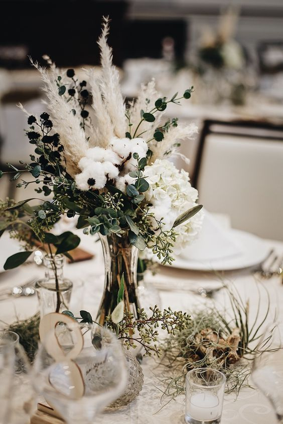 a beautiful wedding centerpiece of cotton, eucalyptus, greenery, white blooms, pampas grass, air plants and table numbers