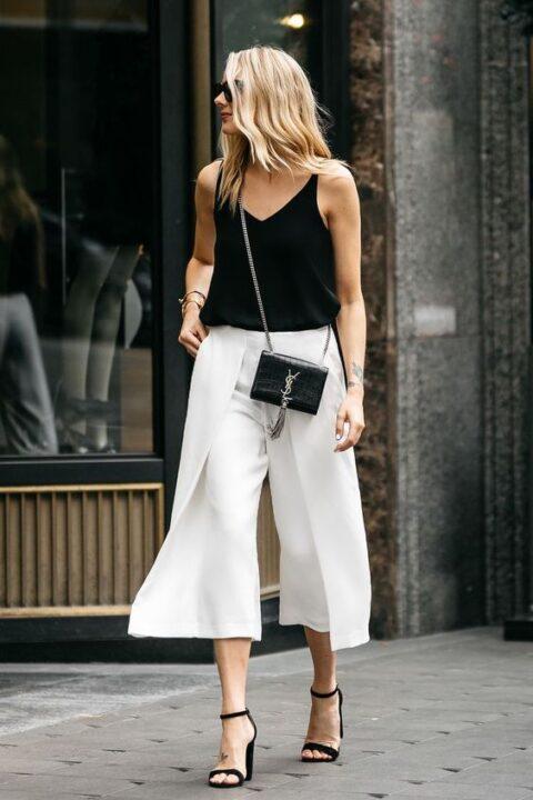 a black top, white wideleg pants, black heels and a mini bag for a chic monochromatic wedding guest look